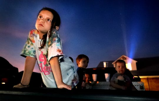 Haiden Jernigan, 7 leans on the tailgate of a pick-up truck as she stands in the back of the truck while the feature movie begins at the Higgins Moonlite Drive-in, on Friday July 19, 2019, in Woodbury, Tenn.