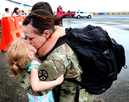 Spc. Katie Byrd, with the 278th ACR kisses her daughter Rosie Byrd, 3, as her other daughter Natalie Byrd, 6 hugs her neck after she gets off the plane at the Volunteer Training Site in Smyrna, from a 9 month overseas deployment on Thursday, May 9, 2019.