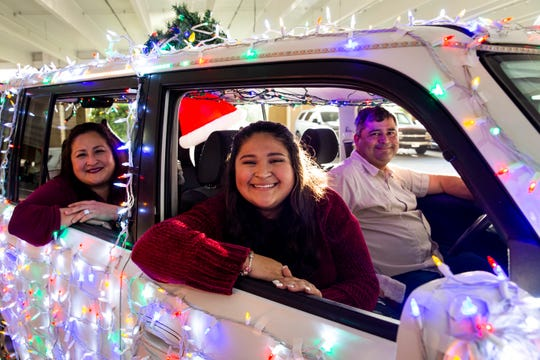 "From left to right, Karla Mendoza, Abigail Mendoza, and José Mendoza pose for a portrait in their ""Christmas car"" at Mercato in Naples on Monday, Dec. 23, 2019. Abigail, who is a junior at Barron Collier High School, says she was embarrassed when her dad first started decorating the car, but now she loves going ""Christmas joyriding"" with him every night."