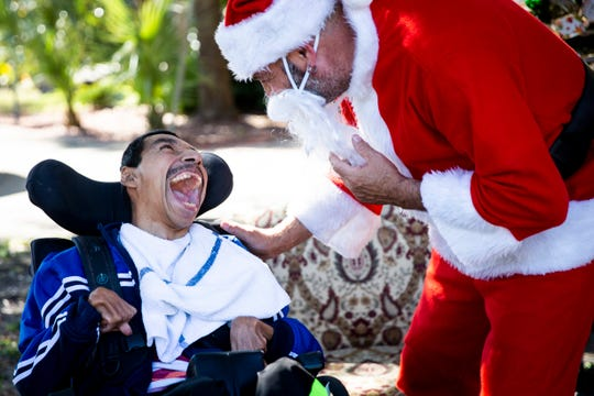 """Pablo Vega, left, smiles as he greets Anthony Baldwin, right, dressed as Santa at Sunrise Community of Southwest Florida in Naples on Tuesday, Dec. 24, 2019. This is Baldwin's fourth year dressing as Santa for the annual Christmas Eve celebration, and he says he keeps coming back because the community is like a family. He loves the joy dressing as Santa brings. """"The smiles on their faces made me glow,"""" he said."""