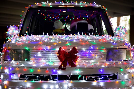 José Mendoza's car is wrapped in around 4,000 LED lights at Mercato in Naples on Monday, Dec. 23, 2019. The Mendozas avoid driving on the main roads with their car lit up, opting instead to drive around bringing Christmas cheer to areas like Victoria Park and Mercato.