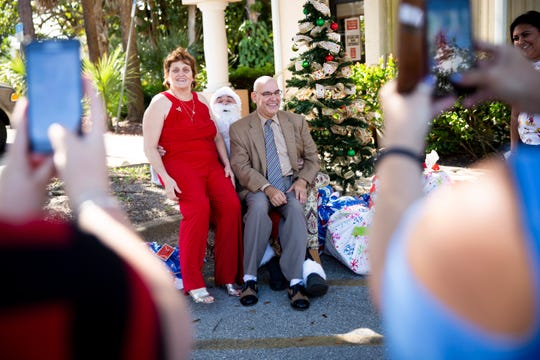 Jane Gutierrez, left, and Hector Lopez, right, pose for photos with Santa as they sit on Anthony Baldwin's lap at Sunrise Community of Southwest Florida in Naples on Tuesday, Dec. 24, 2019.
