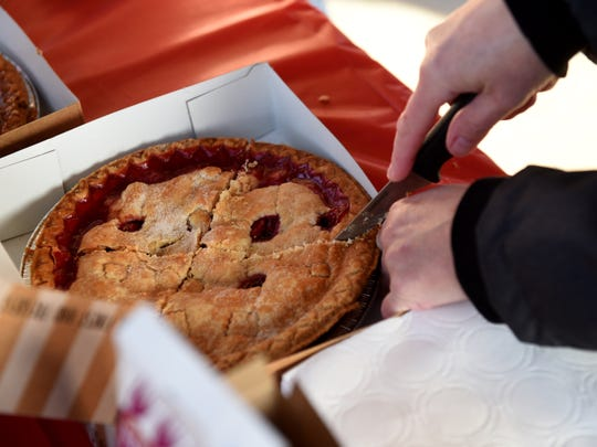 Lucy Holbrook slices up some cherry pie during the Feed Home First event at the Canal Market District on Tuesday, Dec. 24, 2019. For the fifth year shifts of volunteers feed the hungry starting at 9 a.m. and continuing until 7 p.m. Local businesses, families and churches donated food for the meals around the tree at the market.