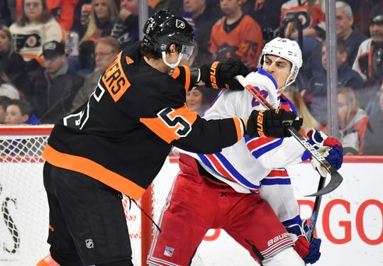 Philadelphia Flyers defenseman Philippe Myers (5) checks New York Rangers left wing Chris Kreider (20) during the first period at Wells Fargo Center.