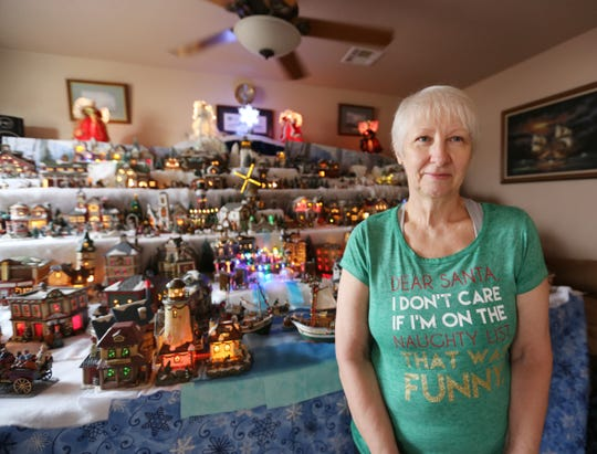 Las Cruces resident Nathalie Fike stands in front of her Christmas village on Dec. 24, 2019. For years, she's been collecting miniature houses, people, boats and other buildings that remind her of favorite places and people.
