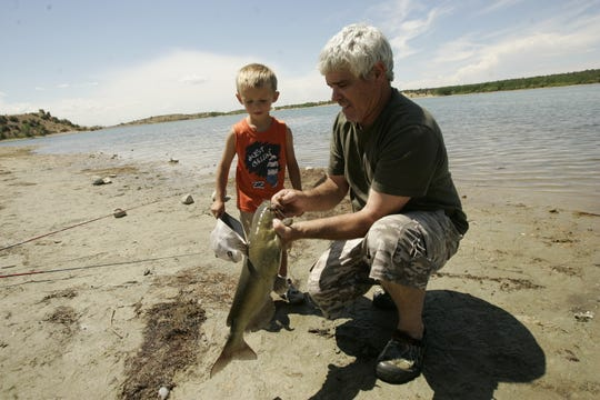 Benny Marionneaux unhooks a catfish he caught in August 2011 at Lake Farmington while his grandson, Jason Sanders, 4, watches.