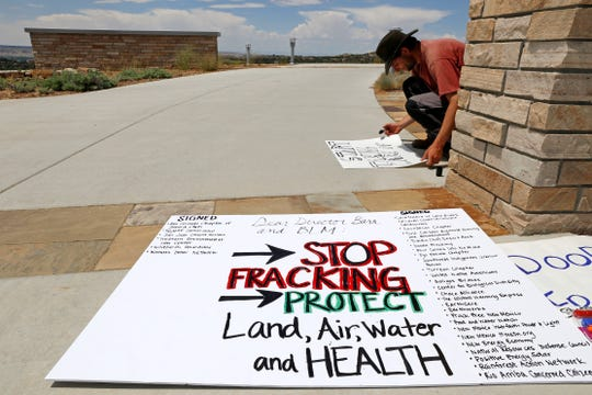 Protesters make anti-fracking signs in June 2015 during a rally against oil and gas drilling near Chaco Culture National Historical Park. The rally took place at the Bureau of Land Management Farmington Field Office.