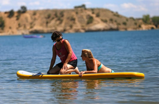 Betty Abrahamson, left, and her daughter Kirstin Abrahamson take a break, Monday, Aug. 15, 2016 while paddleboarding on Lake Farmington.