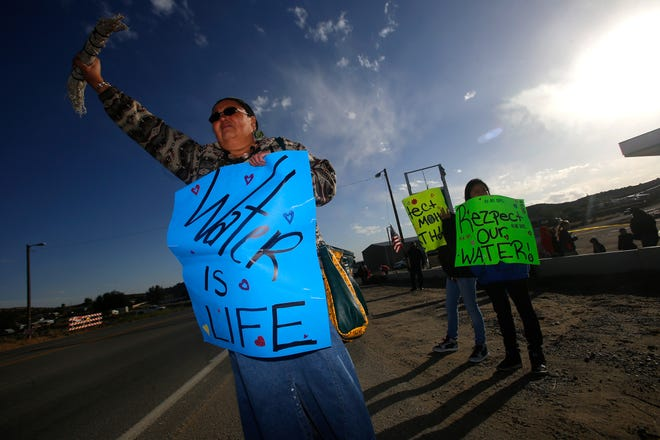 Activist Dawn Dollknife-Teller protests against AV Water Co., Friday, Sept. 23, 2016 at the intersection of County Road 390 and Highway 390 in the Crouch Mesa area.