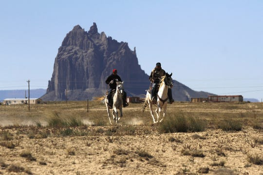 Participants in the Traditional Trail Ride, ride down U.S. Highway 491, Friday, Oct. 4, 2013, towards the Northern Navajo Nation Fair in Shiprock.