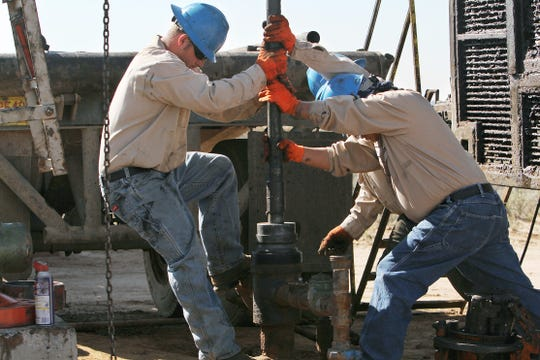 Oil field workers are seen in September 2012.