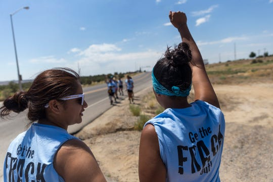 Andreanne Catt, left, and Lauren Howland prepare to join a group of runners protesting oil and gas drilling,  Monday, June 26, 2017 in Farmington.