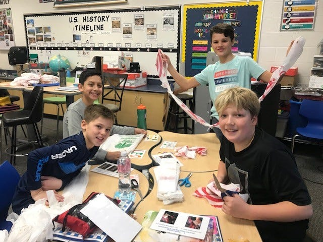 (From left) Dylan Furlani, Gavin McLoughlin, James Liebler and Weston Gardner work on transforming plastic bags into loops and joining them to form plarn (plastic yarn), which will be crocheted into mats for homeless people. All of the fifth graders at Harlan School participated in this service project.
