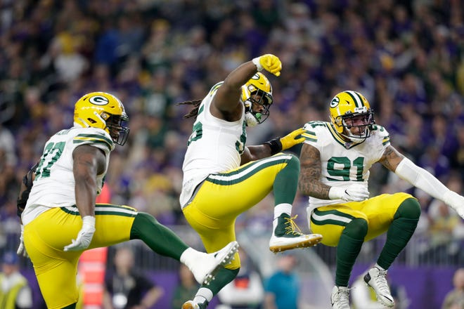 Green Bay Packers' Kenny Clark, left, Za'Darius Smith and Preston Smith celebrate after a sack during the first half of an NFL football game against the Minnesota Vikings, Monday, Dec. 23, 2019, in Minneapolis.