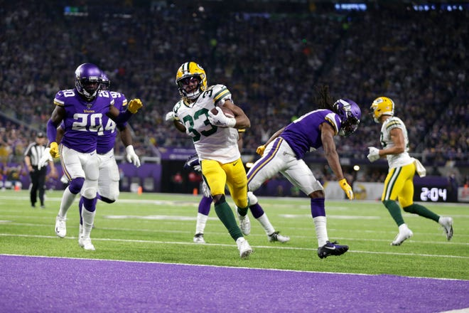 Green Bay Packers running back Aaron Jones (33) scores on a 12-yard touchdown run in the second half of an NFL football game against the Minnesota Vikings, Monday, Dec. 23, 2019, in Minneapolis.