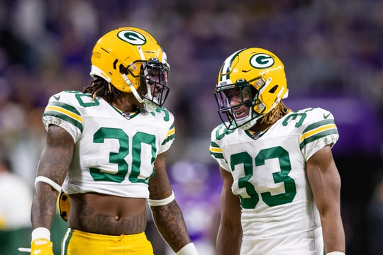 Green Bay Packers running back Jamaal Williams (30) and running back Aaron Jones (33) warm up before a game against the Minnesota Vikings at U.S. Bank Stadium.