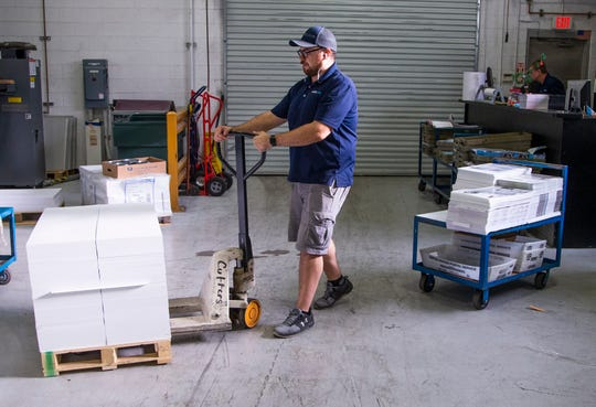 Dillon Redding, a cutter at Mailing.Com , moves a pallet of product at the printing facility in Phoenix, Wednesday, Dec. 11, 2019.