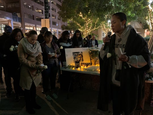 People pray during a candlelight vigil for a woman killed Sunday after crashing into a light-rail train in Phoenix on Dec. 23, 2019.