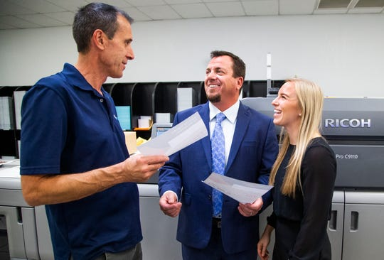 Rob VanWert, a pressman in the digital print room, left, speaks with Mailing.com company owner and CEO Craig Hauer, and marketing director Ashley Jorgensen, at the facility in Phoenix, Wednesday, Dec. 11, 2019.