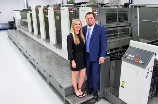 Mailing.com marketing director Ashley Jorgensen and her father, company owner and CEO Craig Hauer, stand near a printing press at the facility  in Phoenix, Wednesday, Dec. 11, 2019.