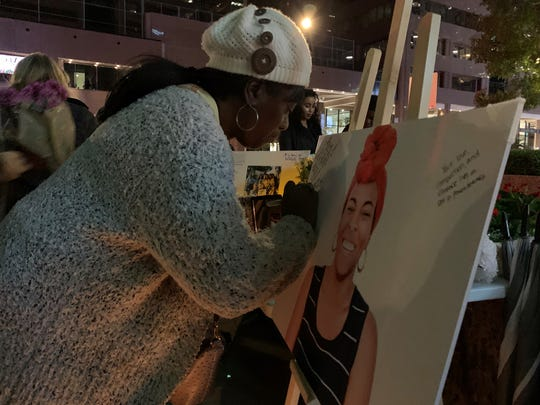People offer condolences during a candlelight vigil for a woman killed Sunday after crashing into a light-rail train in Phoenix on Dec. 23, 2019.