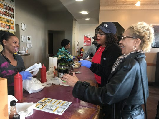 Evangela Stanley, left, owner of People's Choice Kitchen, takes an order from Cheryl Moore, right. Tymisha Williams, center, helped expedite orders.