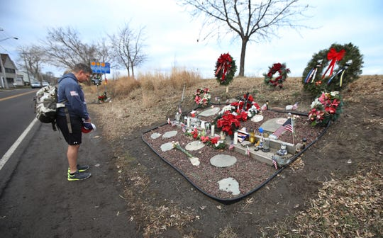 A former neighbor stops to pay his respects at the West Webster memorial on Lake Road in Webster Tuesday, Dec. 24, 2019.  On Christmas Eve 2012, West Webster firefighters Michael Chiapperini and Tomasz Kaczowka were killed in an attack by a lone gunman who had set his house on fire.