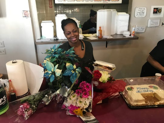 Evangela Stanley, owner of People's Choice Kitchen, 579 Brooks Ave., smiles behind several flower arrangements brought to her on Dec. 24, 2019.
