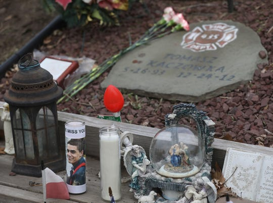 Flowers and candles set at the West Webster memorial on Lake Road in Webster Tuesday, Dec. 24, 2019.  On  Christmas Eve 2012, West Webster firefighters Michael Chiapperini and Tomasz Kaczowka were killed in an attack by a lone gunman who had set his house on fire.