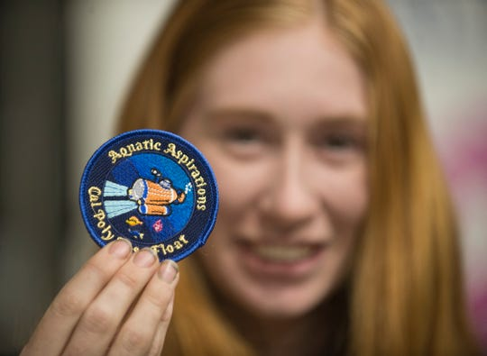 Maddie Toney holds a patch commemorating the 2020 Rose Parade float.