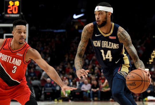 New Orleans Pelicans forward Brandon Ingram, right, drives to the basket on Portland Trail Blazers guard CJ McCollum, left, during the first half of an NBA basketball game in Portland, Ore., Monday, Dec. 23, 2019.