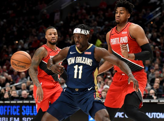 New Orleans Pelicans guard Jrue Holiday, center, loses control of the ball as Portland Trail Blazers guard Damian Lillard, left and center Hassan Whiteside, right, look on during the first half of an NBA basketball game in Portland, Ore., Monday, Dec. 23, 2019.