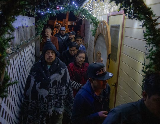 "A group of people make their way into the home after singing ""La Posada,"" a call and response song sung by the people attending the event on Dec. 22, 2019."