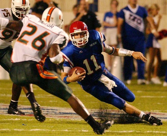 Louisiana Tech quarterback Luke McCown slips trying to get past Miami defender Sean Taylor during a 2003 matchup at Shreveport's Independence Stadium.