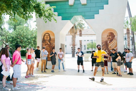 Malachi Taylor, 21, yellow shirt, leads a school tour for prospective students and their families at San Jose State University in July.