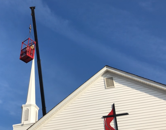 Two employees of J. Bishop Construction Inc. ride in a metal cage to the top of Mount Pleasant United Methodist Church in Millville on Tuesday. Their cargo is a 6-foot cross that was put on top of the just installed replacement steeple. Garton's Rigging provided the ride.