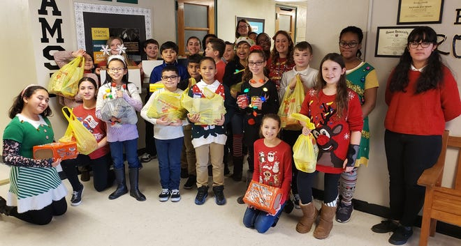 Jennifer Fries' fifth-grade homeroom at Vineland's Applied Math and Science Academy at Johnstone collected the most items for the academy's December commitment to kindness project. They are pictured with Pastor Heather Sugden from Redeemer Lutheran Church in Vineland who accepted the donations on behalf of the Vineland Ministerium Food Bank.