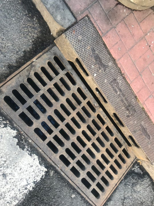 The drain in front of Chicken Hut in Mount Vernon, where a worker last week dumped kitchen waste. The imprint atop the drain reads DUMP NO WASTE DRAINS TO WATERWAYS