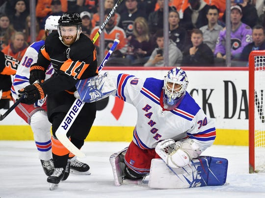 Dec 23, 2019; Philadelphia, Pennsylvania, USA; Philadelphia Flyers center Sean Couturier (14) battles against New York Rangers goaltender Henrik Lundqvist (30) during the second period at Wells Fargo Center. Mandatory Credit: Eric Hartline-USA TODAY Sports