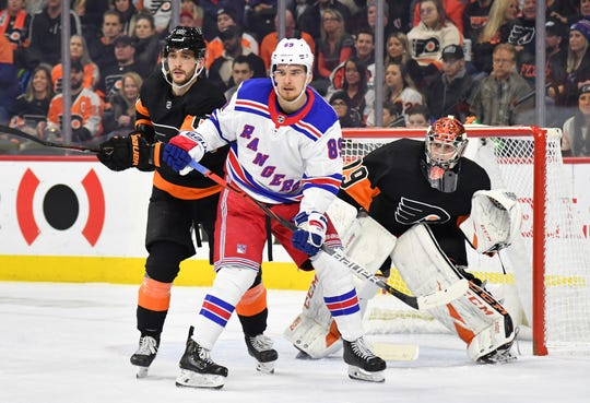 Dec 23, 2019; Philadelphia, Pennsylvania, USA; New York Rangers right wing Pavel Buchnevich (89) with Philadelphia Flyers defenseman Shayne Gostisbehere (53) in front of  goaltender Carter Hart (79) during the first period at Wells Fargo Center. Mandatory Credit: Eric Hartline-USA TODAY Sports