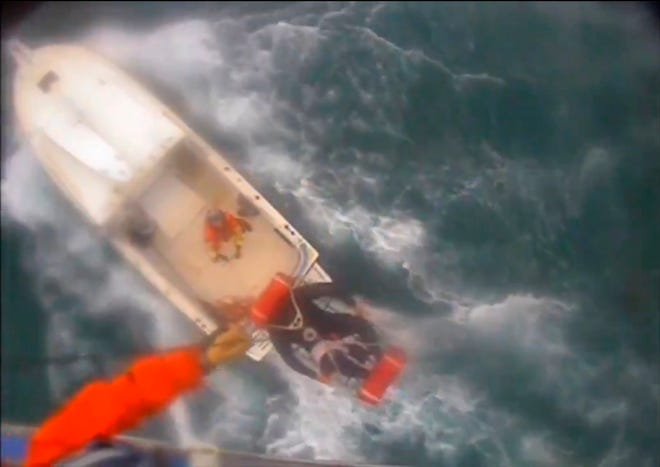 In this Saturday afternoon, Dec. 21, 2019, video image released by the U.S. Coast Guard shows a man, wearing a full-body wetsuit, being hoisted up from the boat into the helicopter near Santa Rosa Island, one of the Channel Islands in Southern California.