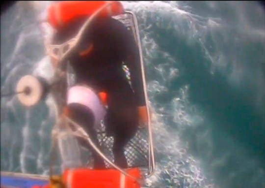 This Saturday video image released by the U.S. Coast Guard shows Adam Coons, wearing a full-body wetsuit, being hoisted up from the boat into the helicopter near Santa Rosa Island.