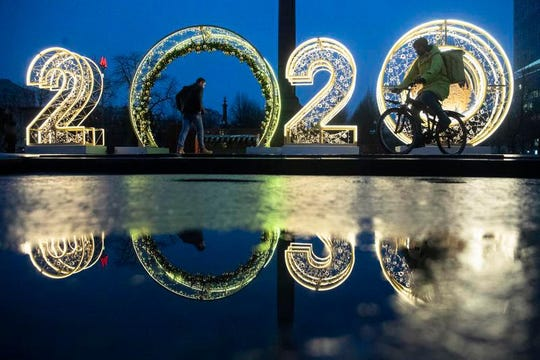 People walk in front of 2020 numbers of the upcoming new year decorated for Christmas and New Year celebrations in Novy Arbat street in Moscow, Russia, Wednesday, Dec. 25, 2019. (AP Photo/Alexander Zemlianichenko)