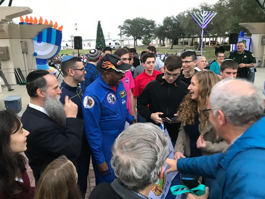 Former Nasa astronaut Winston Scott talks with Israel and American students at Sunday's Hanukkah celebration in Cocoa.