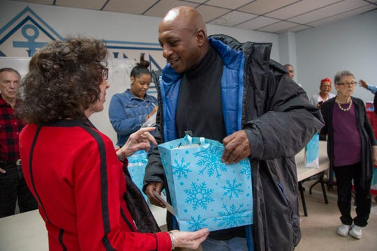 Mitzvah Day volunteer Irene Sinclair of Southfield, left, hands Antonio Smith, 57, of a gift bag at Detroit's Mariners Inn.
