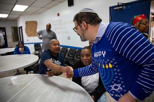 Lee Howell, 58, of Detroit and a resident at Mariners Inn, left, shakes hands with Rabbi Asher Lopatin of the Jewish Community Relations Council at the agency's annual Christmas Day gathering Wednesday, before receiving gifts handed out by Mitzvah Day volunteers.