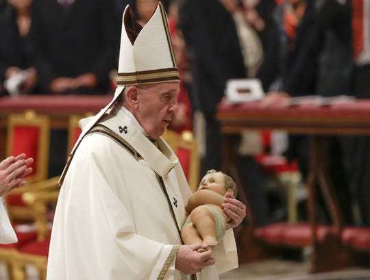 Pope Francis holds a statue of Baby Jesus as he leaves after celebrating Christmas Eve Mass in St. Peter's Basilica at the Vatican, Tuesday, Dec. 24, 2019.