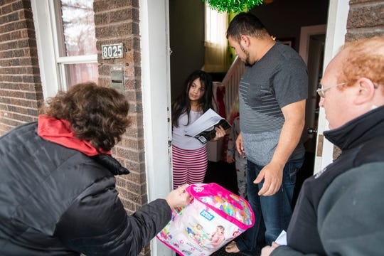Larisa Ponce, 8, and her father Elvin Ponce get a surprise visit and free toys from Jimmy's Kids volunteers Adrienne Lenhoff and Jack Cohen on Christmas Day.