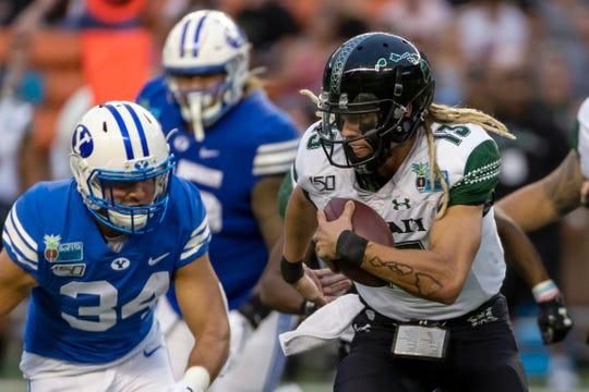 Hawaii quarterback Cole McDonald runs as BYU linebacker Kavika Fonua (34) gives chase.