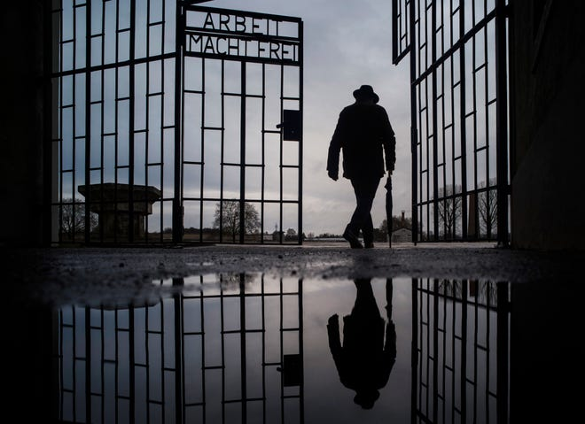 """A man walks through the gate of the Sachsenhausen Nazi death camp with the phrase """"Arbeit macht frei"""" (work sets you free) in Oranienburg, Germany, on International Holocaust Remembrance Day, Jan. 27, 2019."""